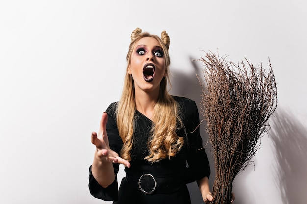 Fair-haired witch with dark makeup screaming on white wall. angry vampire in black dress .