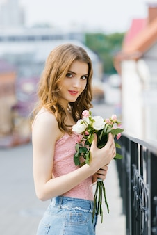 A fair-haired young beautiful pretty girl in summer clothes stands and holds delicate white and pink roses in her hands after a date