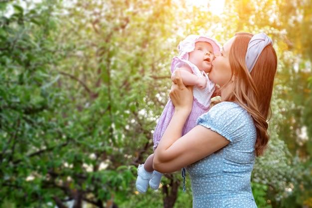 青いドレスを着た金髪の若い女性は、小さな娘を腕に抱き、春の日、日光の緑の公園で幸せな笑顔で赤ちゃんの頬にキスします。