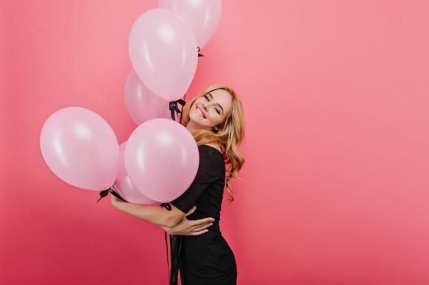 明るい壁に幸せな笑顔でポーズをとる金髪の若い女性。風船を持って喜んでいるヨーロッパの誕生日の女の子の屋内写真。