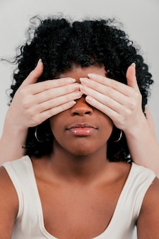 Fair skinned hands of woman closing the eye of an african woman