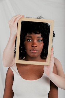 Fair skinned hands of woman holding wooden border frame in front of an african woman