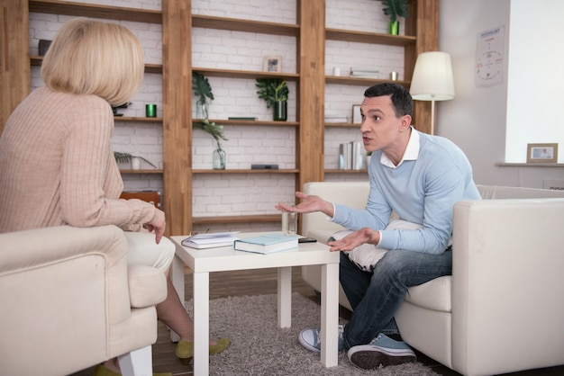 Not fair. worried disquieted man chatting with psychologist while posing on sofa