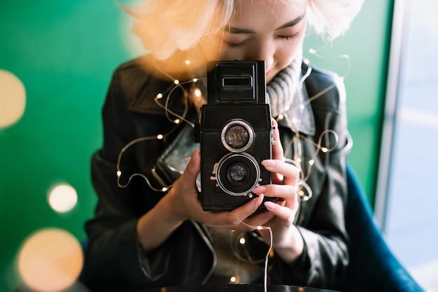 Молодая белокурая азиатская женщина держа винтажную камеру фильма с fairy светами и bokeh вокруг, селективный фокус