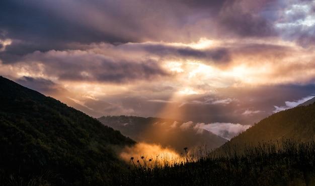 山の劇的な空と太陽光線のある妖精の風景。夕日の背景