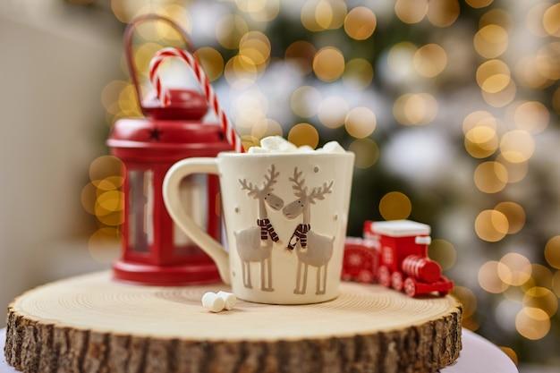 フェアリーライトの背景、マシュマロとホットココア、木製のカットと赤いランタンに鹿と白いカップ、クリスマスと新年の休暇中に自宅で子供たちの列車。ソフトフォーカスボケ。