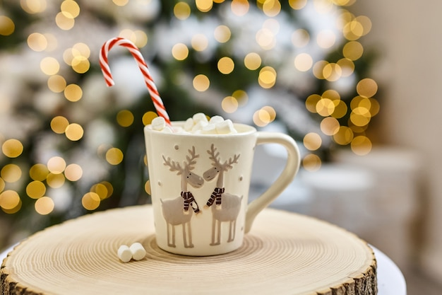 フェアリーライトの背景、マシュマロとホットココア、クリスマスと新年の休暇中に自宅で木製のカットに鹿と白いカップ。ソフトフォーカスボケ。