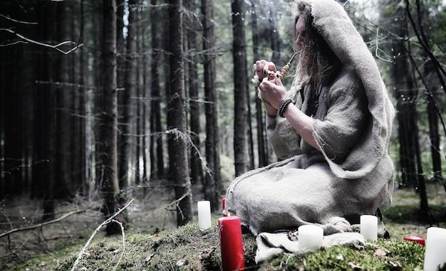 Сказочный волшебник. колдун со стеклянной сферой, магическое заклинание и ритуал. старец с посохом и крестом в лесу. черная и белая магия. заклинание в старой книге.