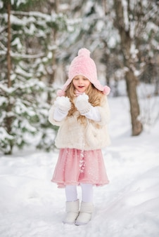Fairy tale beautiful girl in a white fur coat pink hat snow in her hands