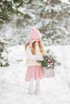 Fairy tale a beautiful girl in a white fur coat with a white big basket with fir branches in a winter snow-covered forest.