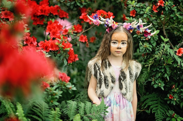 Fairy tale girl. portrait a little girl in a deer dress with a painted face in the forest