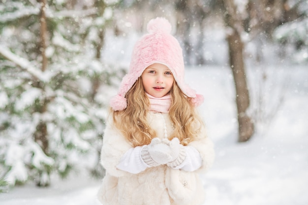 Fairy tale portrait of a beautiful girl in a white fur coat pink snow hat in her hands.