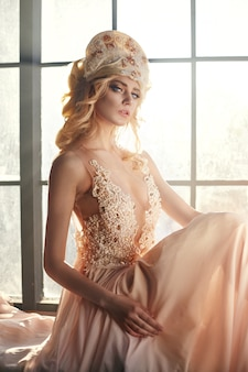 Fairy with long blonde hair in light is on background of a large window