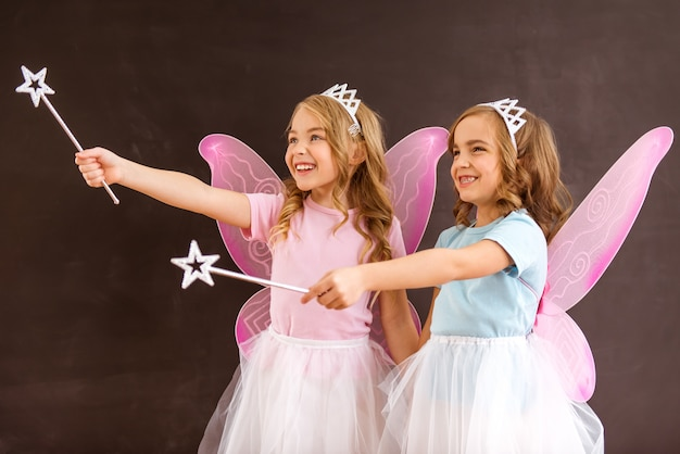 Fairy with pink wings holding forward their magic wands.