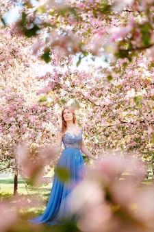 파란 이브닝 드레스에 빨간 머리를 한 동화 소녀는 화창한 날 흐릿한 전경 알레르기가 없는 개념에 분홍색 벚꽃 정원을 걷습니다.