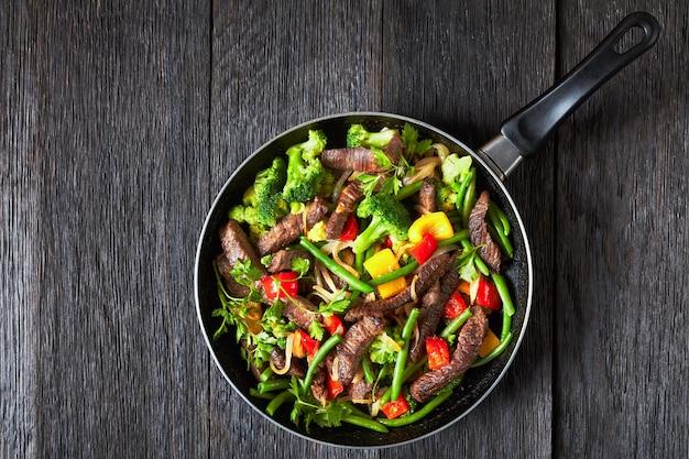 黄色と赤のピーマン、パセリ、タマネギ、インゲン、ブロッコリーを添えたファヒータビーフステーキを、ダール木製テーブルのフライパンで提供、上面図、フラットレイ、コピースペース