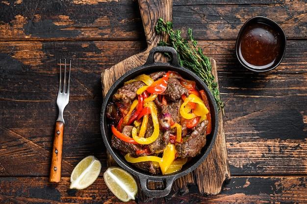 Традиционное мексиканское блюдо из говядины фахитас на сковороде. темный деревянный фон. вид сверху.
