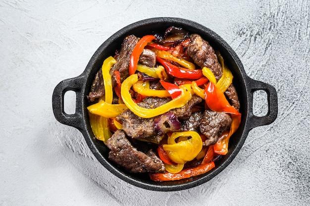 Традиционное мексиканское блюдо из говядины фахитас на сковороде
