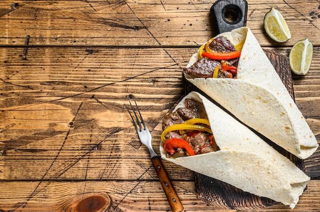 Обертка fajitas tortilla с полосками говяжьего мяса, цветным болгарским перцем, луком и сальсой. деревянный фон. вид сверху. скопируйте пространство.