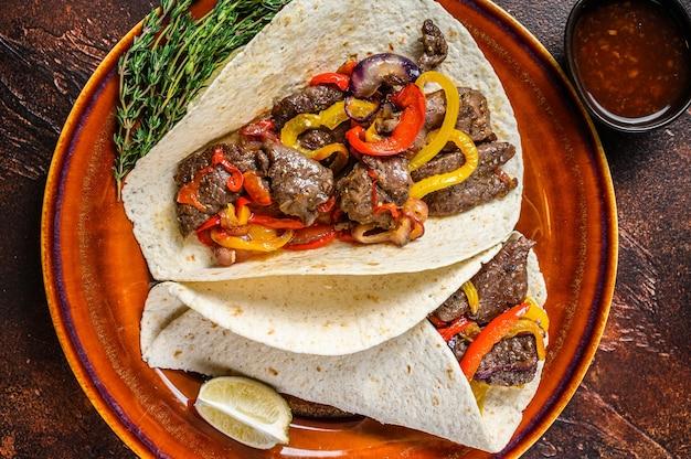 Fajitas tortilla는 쇠고기 고기 스테이크 줄무늬, 달콤한 고추 및 양파로 포장됩니다. 어두운 나무 테이블. 평면도.