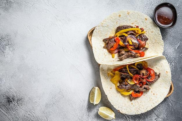 Фахитас с полосками говядины, цветным болгарским перцем и луком, подается с лепешками и сальсой