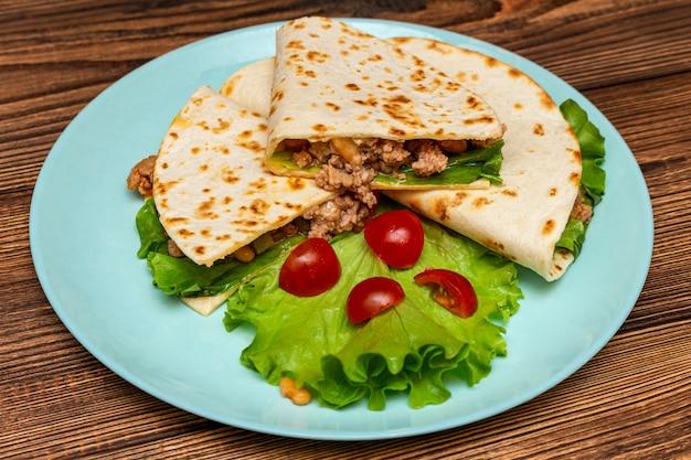 青いプレートの暗い木製のテーブルにコーントルティーヤのひき肉野菜とファヒータ。ファーストフードの伝統的な食べ物のコンセプト