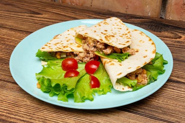 ブループレートにトウモロコシのトルティーヤにひき肉の野菜とファヒータ。
