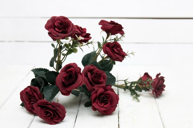 白い背景で隔離赤いバラの偽の花束。