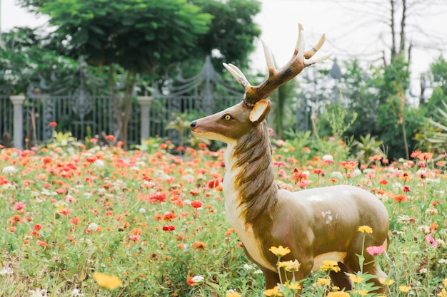 The fake deer statue stands in the middle of the flower garden.
