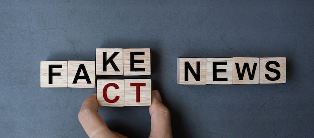 Fake to fact news word on table background.