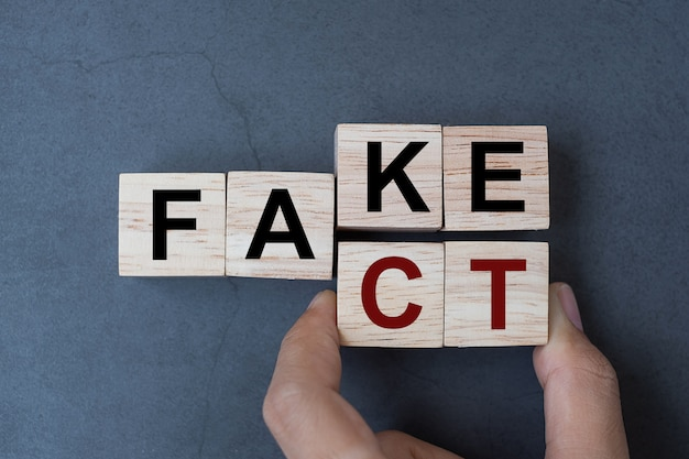 Fake to fact word on table background.