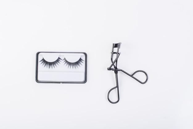 Fake false eyelash with curler isolated on white background.