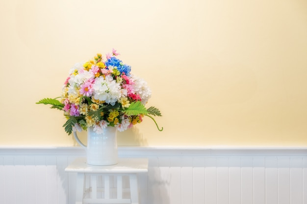 Fake flowers for interior decoration on white wood with cream wall in background.