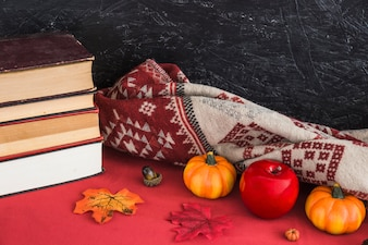 Fake fruits and blanket near books and leaves