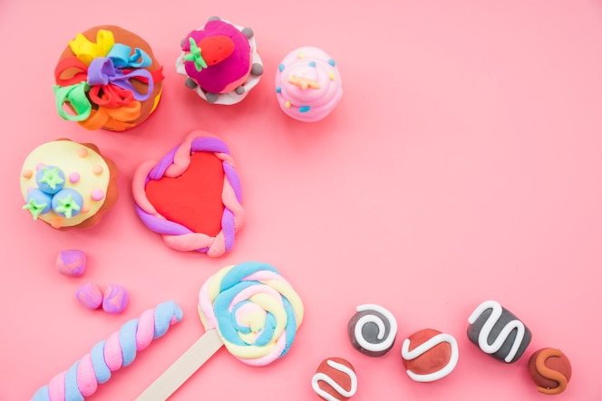 Fake handmade cookies and cake made with clay on pink background
