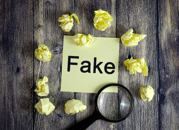 Fake is written on a yellow sticker. fact selection, search with a magnifying glass