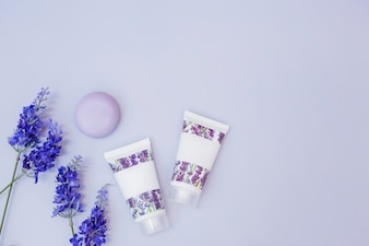 Fake lavender flower; soap and moisturizing cream on colored background