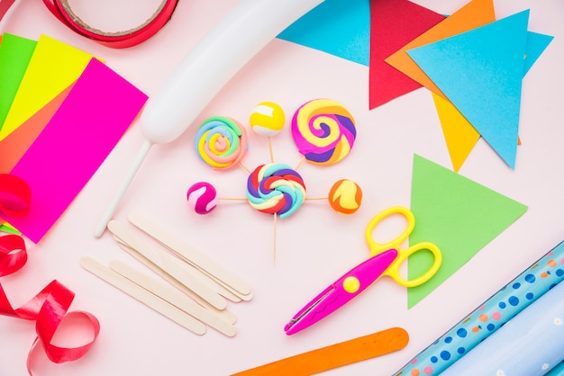 Fake lollipop with crafts equipment with scissors on pink background