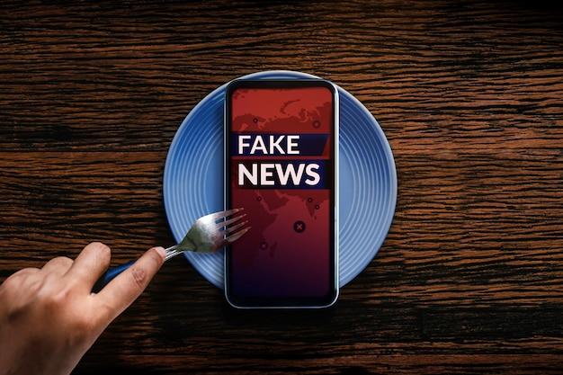 偽のニュースのコンセプト。毎朝、朝食を食べるように携帯電話やソーシャルメディアから毎日の偽のニュースを読む。比喩