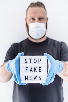 Covid-19パンデミックコンセプト中のフェイクニュースインフォデミック。保護マスクと医療用手袋を着用している男性