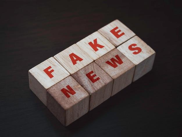 偽のニュース、暗い背景の木製の立方体ブロックの赤い言葉。偽物、信用の失墜、嘘、混乱、煽動、歪みの概念。