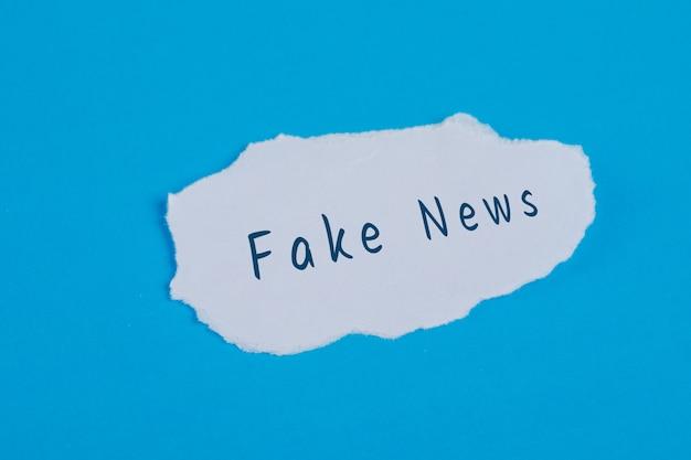 Testo falso di notizie su carta lacerata sulla disposizione blu del piano della tavola.