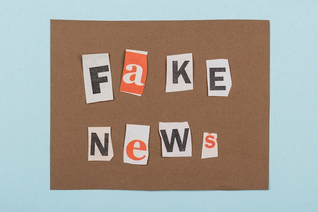 Fake news with paper pieces top view
