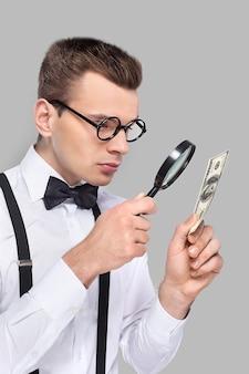 Подделка или настоящая? портрет веселого молодого человека в галстуке-бабочке и подтяжках, смотрящего через увеличительное стекло на долларовую купюру, стоя на сером фоне