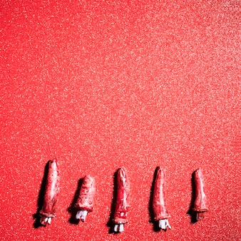Fake scary fingers over red glitter background