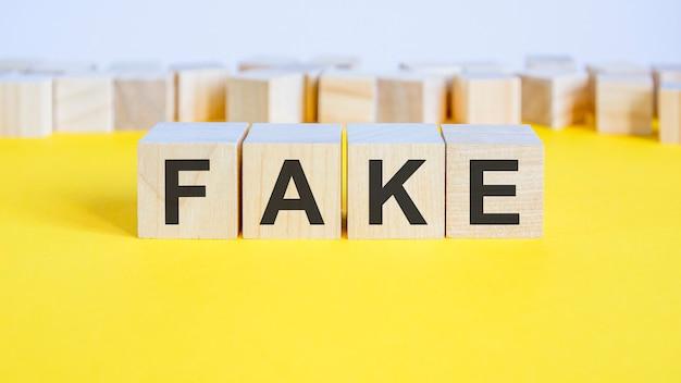 黄色いテーブルの上に横たわっている木製のブロックに偽の言葉。文字が周りにあるビジネスコンセプトのおもちゃのブロック。セレクティブフォーカス