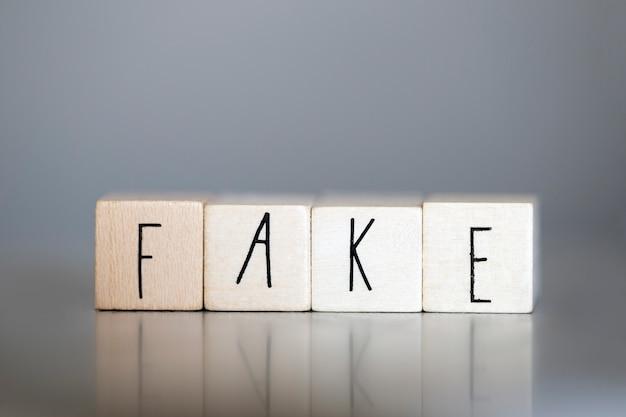 Деревянный куб со словом fake на серой стене, бизнес и дизайн-концепция
