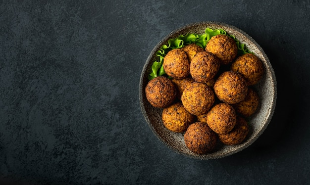 Falafel balls in a ceramic bowl on a black table, top view, copy space