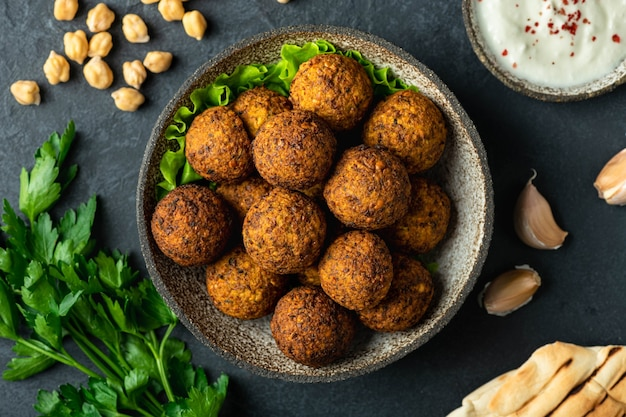 Falafel balls in a ceramic bowl on a black table, top view