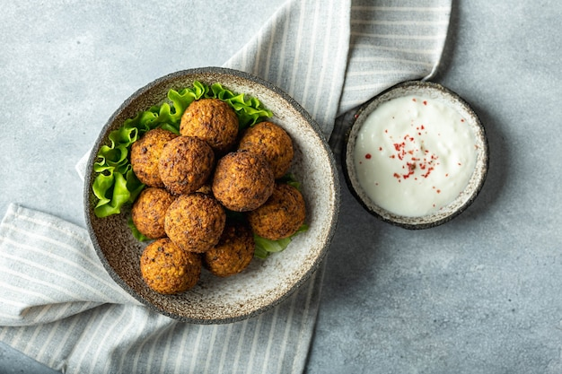 Falafel balls in a ceramic bowl on a concrete background top view